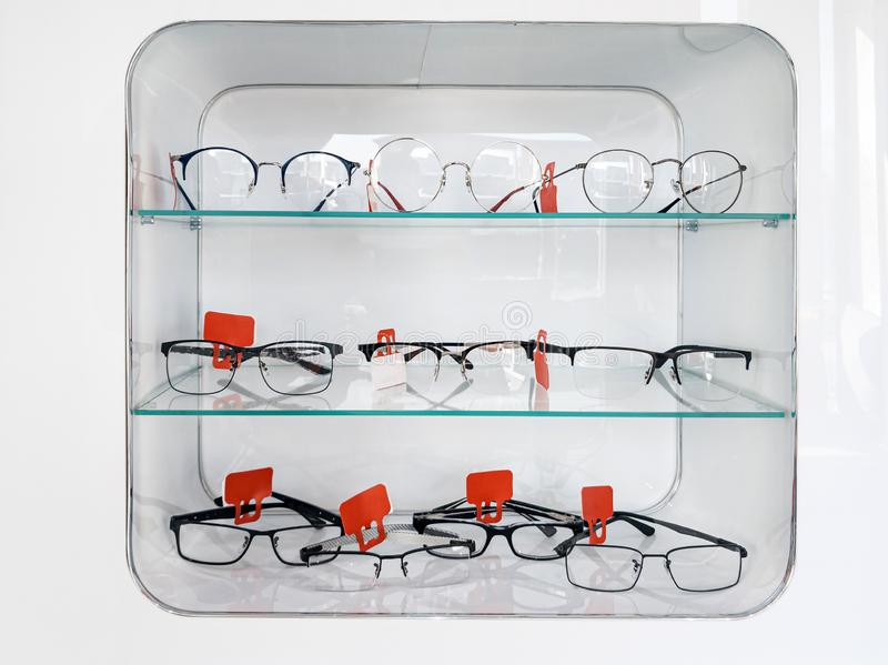 Schuif met glazen rekken met bril en frames in de optische winkel om het gezichtsvermogen te verbeteren en de ogen te corrigeren  stock fotografie