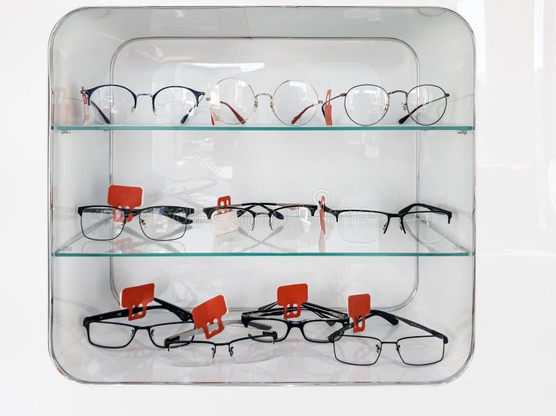 Schuif met glazen rekken met bril en frames in de optische winkel om het gezichtsvermogen te verbeteren en de ogen te corrigeren  royalty-vrije stock fotografie