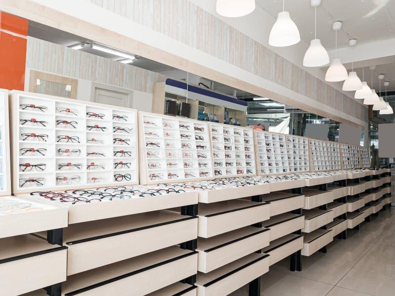 Schuif met glazen rekken met bril en frames in de optische winkel om het gezichtsvermogen te verbeteren en de ogen te corrigeren  royalty-vrije stock afbeelding