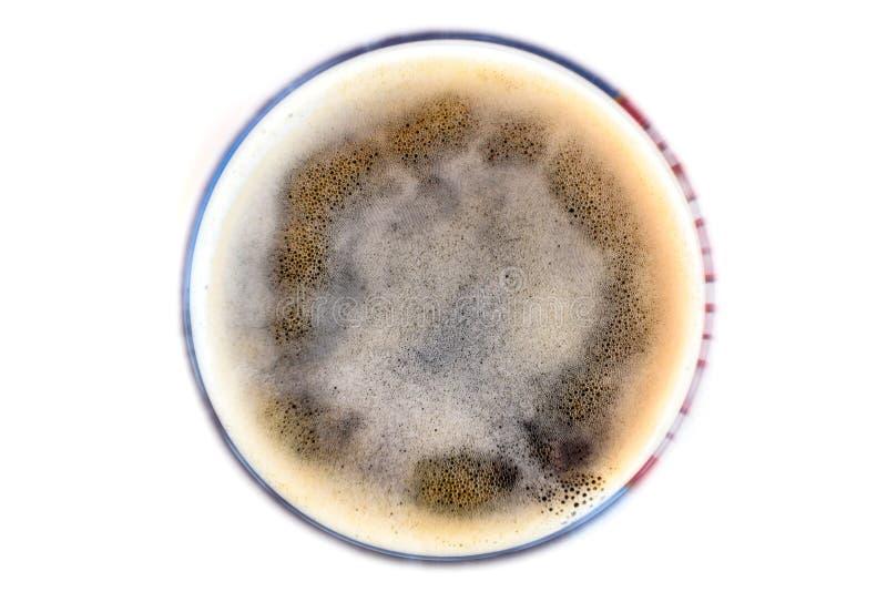 Schuim in glas donker bier op de witte lijst stock fotografie