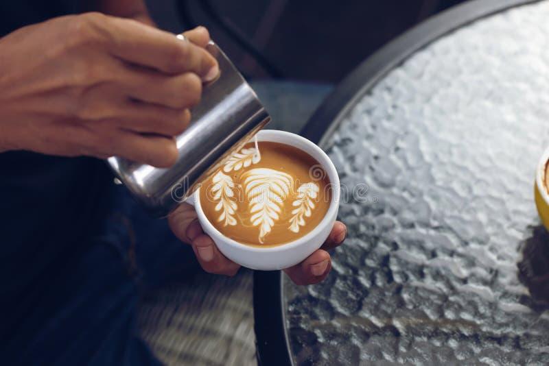 Schuim van de Barista het gietende melk voor het maken van koffie latte kunst met patte stock foto's