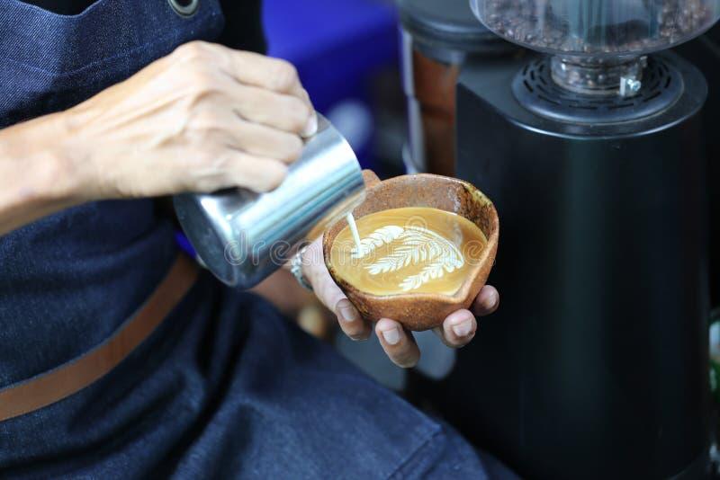 Schuim van de Barista het gietende melk voor het maken van koffie latte kunst met patte royalty-vrije stock fotografie
