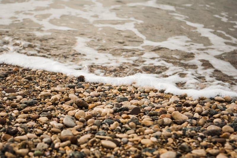Schuimend golven op een rotsachtige kust, sluit omhoog Landschap op een bewolkte dag Mening van kalme overzees met golven en rots royalty-vrije stock foto