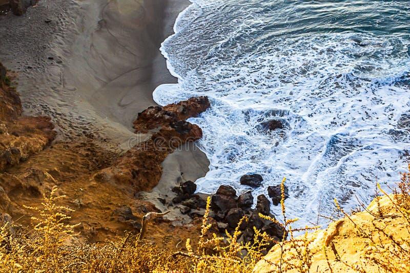 Schuimende golf op zandig die strand met rotsen, door klippengezicht en onkruid worden gevoerd stock afbeelding