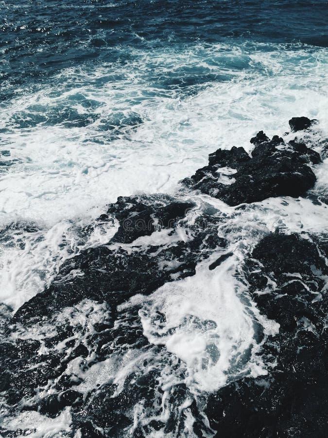 Schuimende golven bij oceaankust bij zonsondergang royalty-vrije stock afbeelding