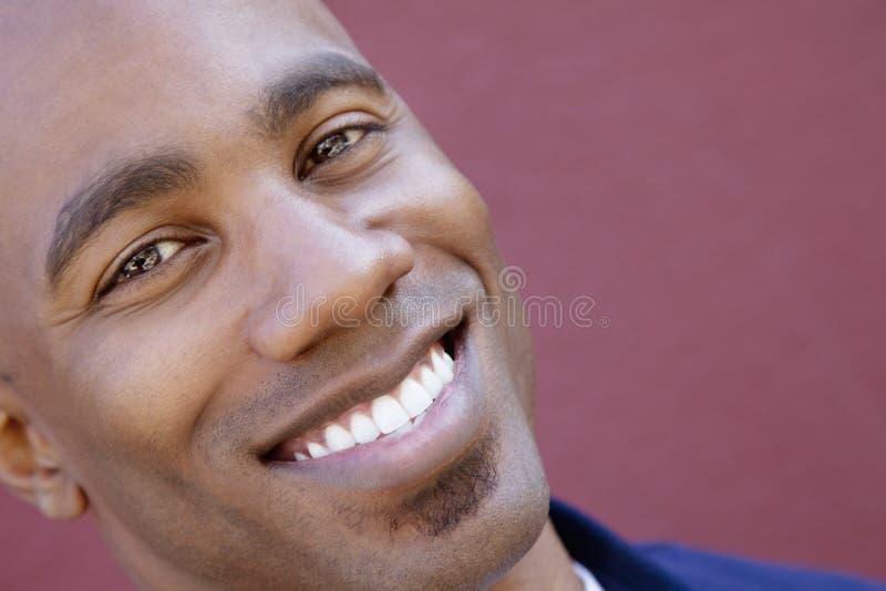 Schuine standportret van een gelukkige Afrikaanse Amerikaanse mens over gekleurde achtergrond royalty-vrije stock foto's