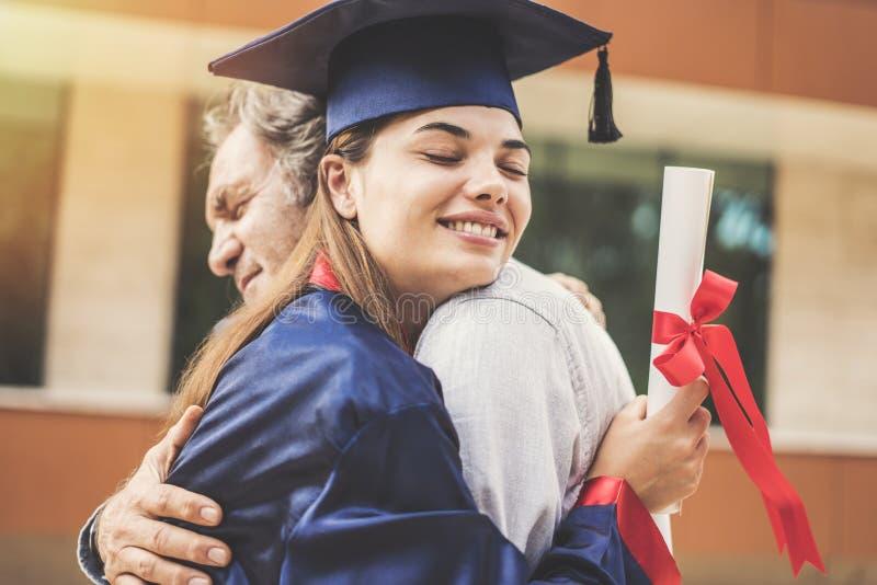 Schulabgänger, der ihren Vater umarmt stockfoto