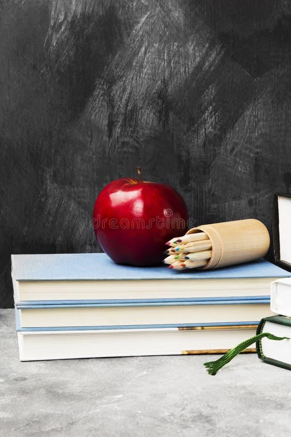 Schulattribute - Bücher, farbige Bleistifte, Notizbuch, Apfel auf d stockfoto