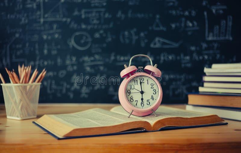 Schulbücher auf Schreibtischformeln und Physikaufschrift auf dem bla stockbilder