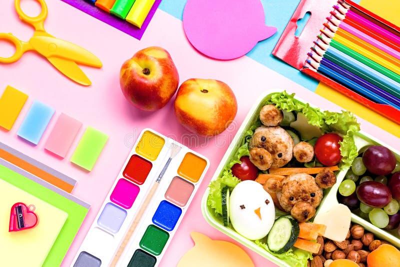 Schulbedarf, buntes Briefpapier, Rucksack und Lunchbox mit lustiger Nahrung für Kinder Zurück zu Schulkonzept ausbreiten lizenzfreie stockfotografie