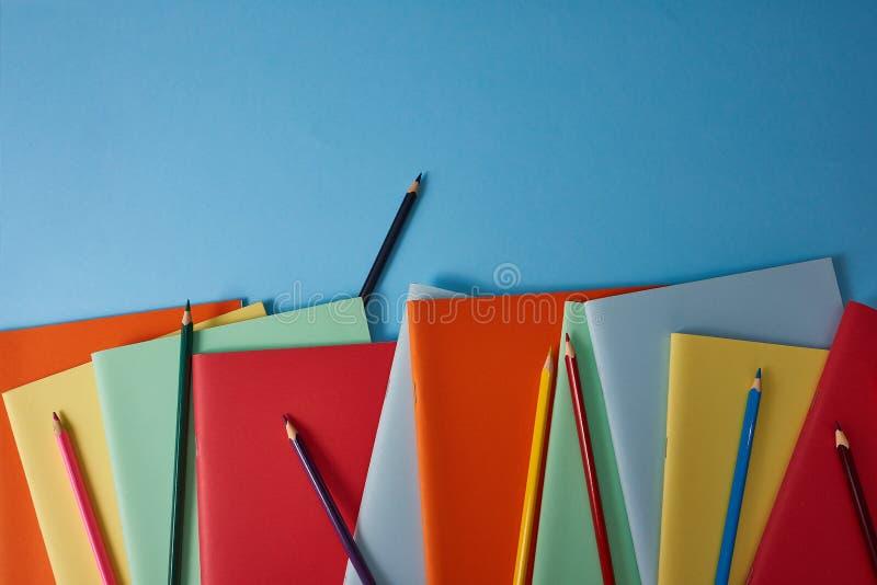 Schulbedarf mit bunten Bleistiften und Notizbüchern lizenzfreie stockbilder