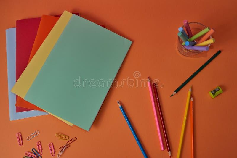 Schulbedarf mit bunten Bleistiften und Notizbüchern stockbilder