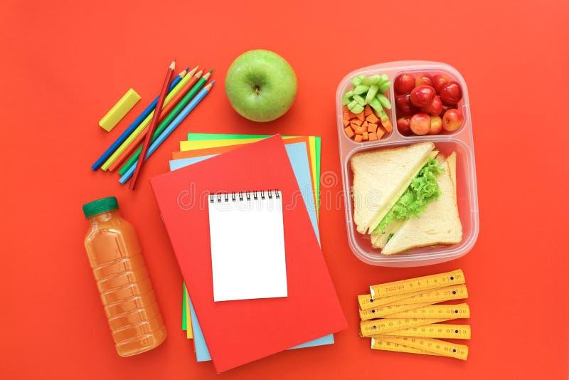 Schulbedarf und Brotdose mit Sandwichen, Stücken Gurken und Karotten, Aprikose, Kirschen, Apfel, Flasche von lizenzfreies stockbild