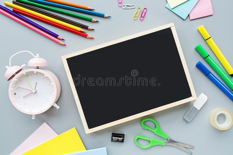 Schulbedarfbriefpapier, Farbbleistifte, Papier, Wecker auf grauem Hintergrund, zurück zu Schulkonzept mit Kopienraum für Text stockbilder