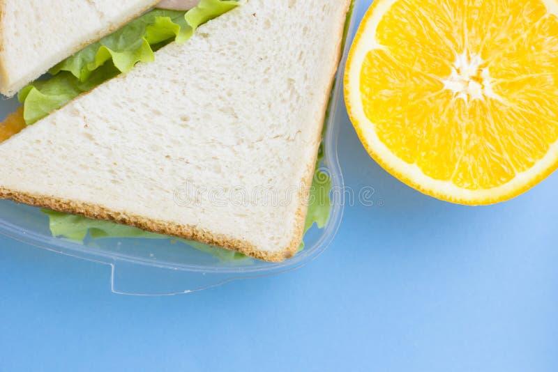 Schulbrotdose Brot, Orange, Süßigkeiten, Babykörner, Karotte und Tomaten im grünen Plastikbehälter stockfotografie