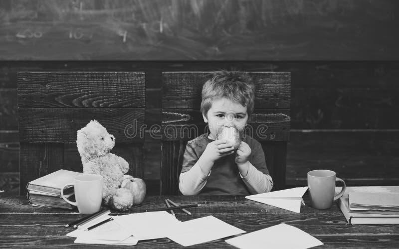 Schulbruch Hungriges Kind, das Apfel im Klassenzimmer isst Kleiner Junge, der mit Papierfläche spielt stockfotografie