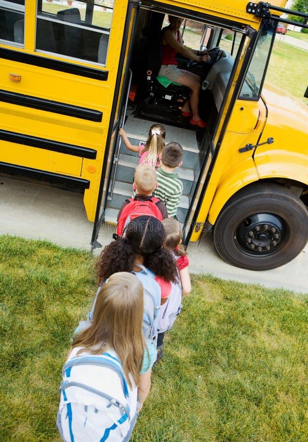 Schulbus: Kinder, die in Bus einsteigen stockbilder