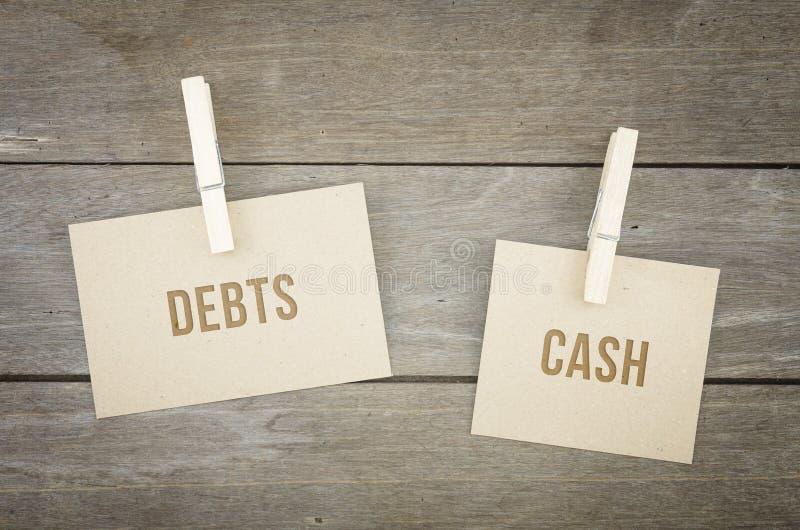 Schulden oder Bargeld, Geschäftsbegriffswörter, hölzerner Hintergrund mit Blättern des braunen Papiers oder Anmerkung stockbilder