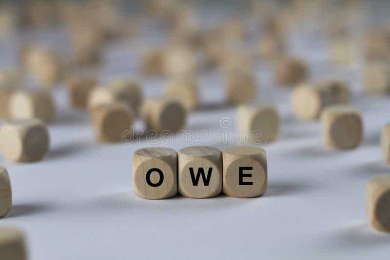 Schulden Sie - Würfel mit Buchstaben, Zeichen mit hölzernen Würfeln stockbilder