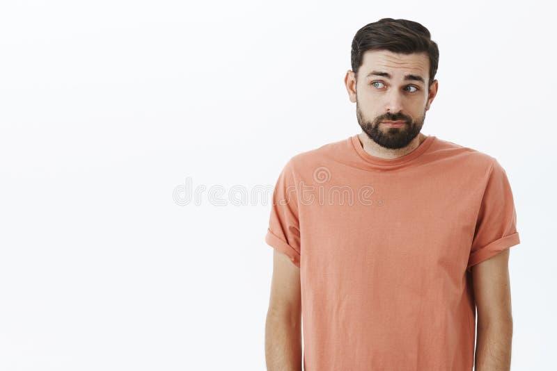 Schuldige en schuwe mannelijke medewerker die bij verbergende ogen, kijkend linker, het buigen, het maken van lichte shug en het  stock afbeeldingen