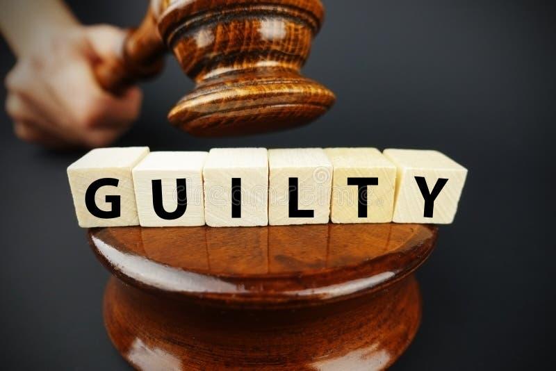 Schuldiges Gerichtsurteil mit Richterhammer und hölzernen Würfeln mit Text stockbilder