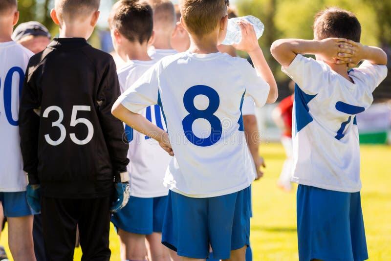 Schule Team Sports Tournament Jungen-Fu?ball-Spieler-Trinkwasser von einer Wasser-Flasche stockfotos