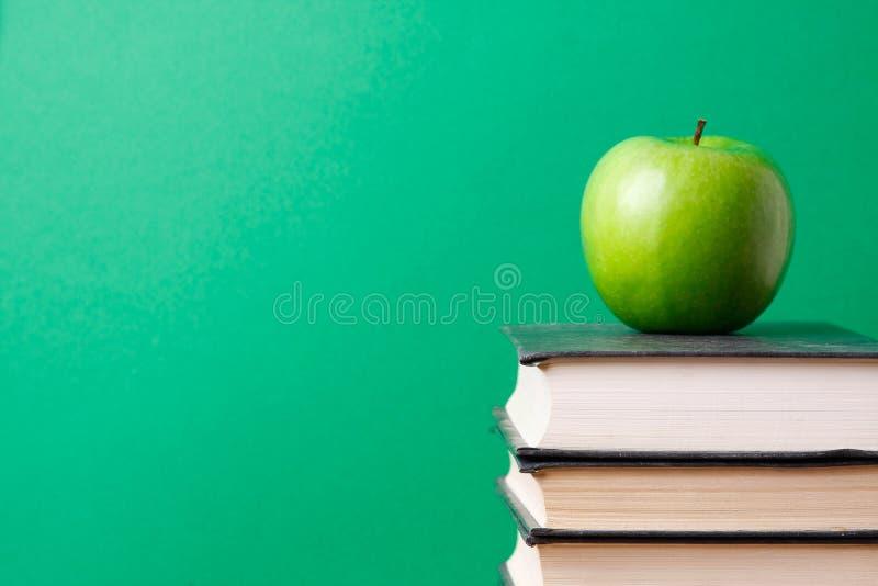 Schulebücher mit Apfel lizenzfreie stockbilder
