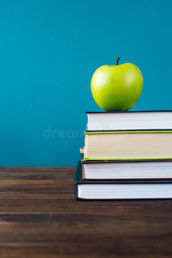Schuleb?cher mit Apfel auf Schreibtisch lizenzfreies stockfoto