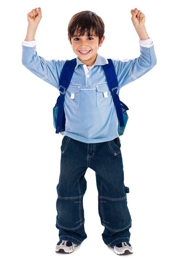 Schulejunge, der seine Hände oben tragen Schulebeutel anhebt stockfotos