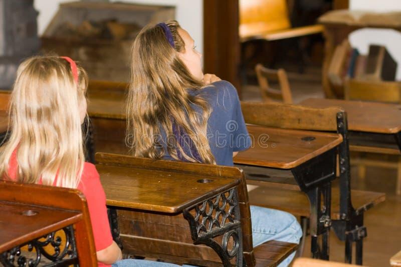 Schulekinder in den Schreibtischen. stockbild