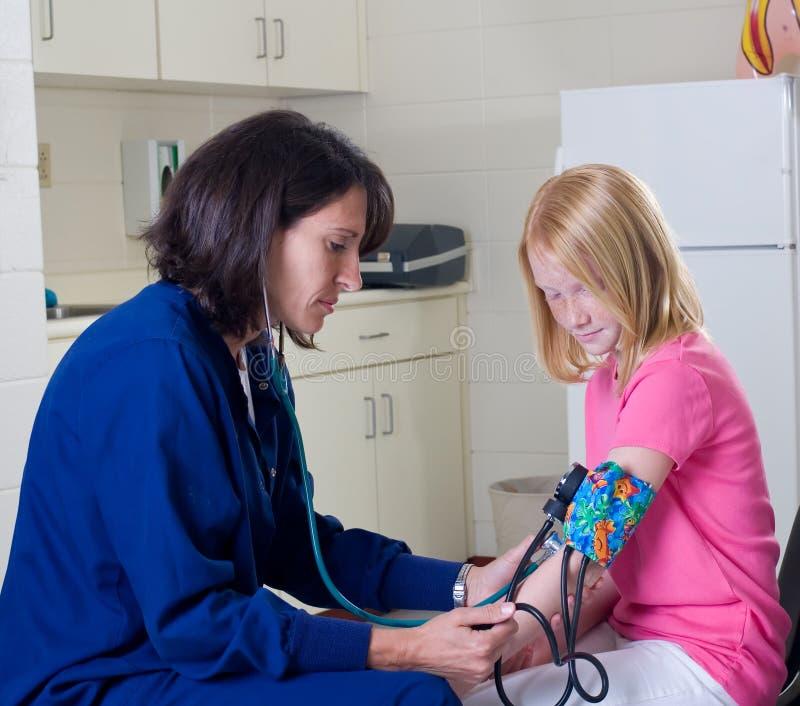 Schulekrankenschwester, die Blutdruck überprüft lizenzfreies stockfoto