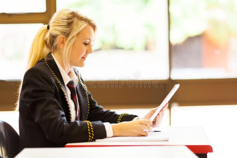Schulemädchen, das Tablettecomputer verwendet lizenzfreie stockfotografie
