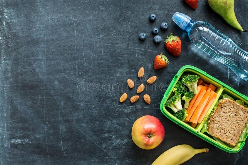 Schulen Sie Brotdose mit Sandwich, Gemüse, Wasser und Früchten stockbilder