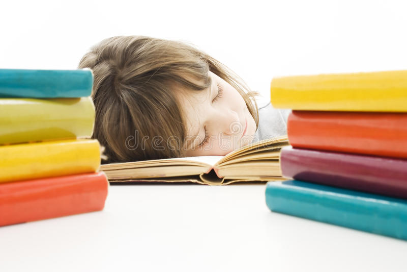 Schulen Sie das Mädchen, das am Schreibtisch studiert, der müde ist. lizenzfreie stockbilder