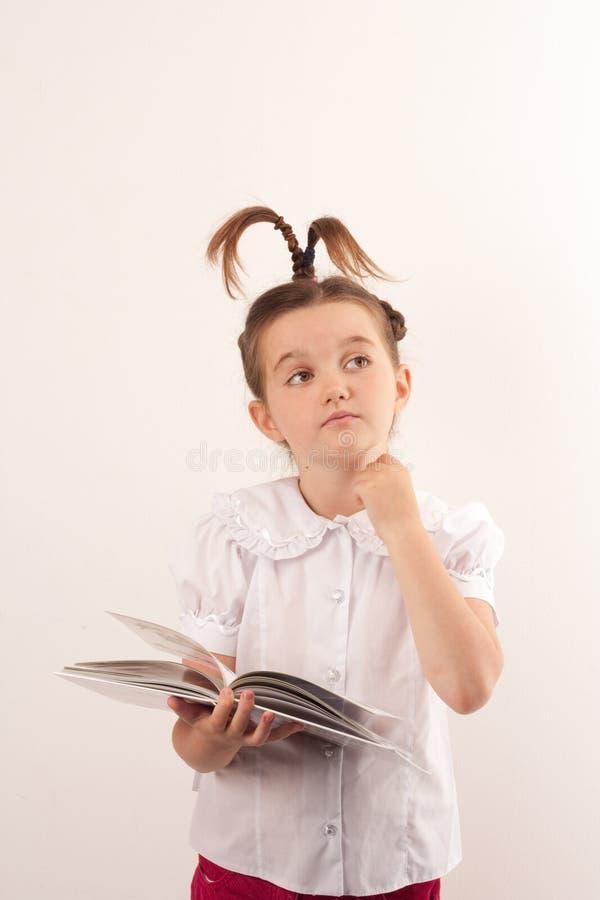 Schulen Sie das Mädchen mit lustiger Haarart ein Buch lesend lizenzfreie stockfotografie