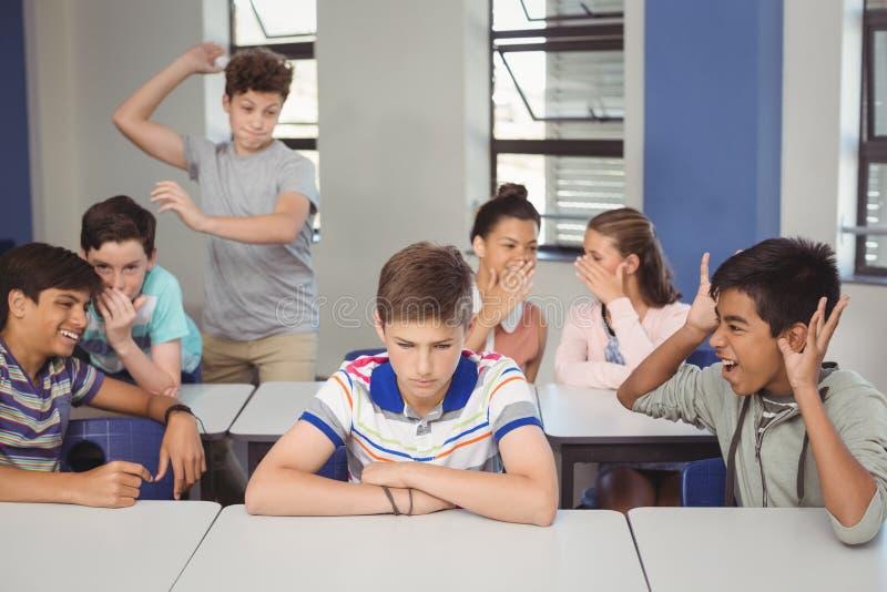 Schulen Sie die Freunde, die einen traurigen Jungen im Klassenzimmer einschüchtern lizenzfreies stockfoto