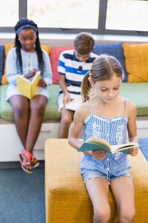 Schulen Sie die Kinder, die auf Sofa und Lesebuch in der Bibliothek sitzen stockbilder