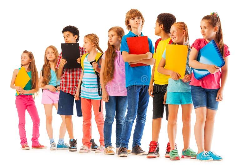 Schulen Sie die Kinder, die in der Linie mit Büchern stehen lizenzfreie stockbilder