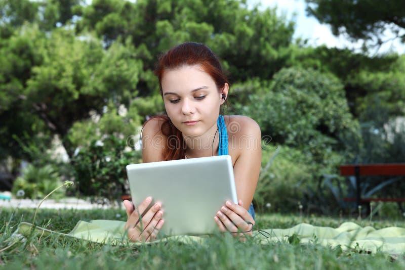 Schulen Sie Mädchen am Park mit Tablette und Kopfhörer lizenzfreie stockfotos