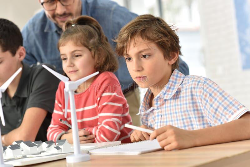 Schulen Sie Schüler in der Klasse, die über natürliche Energiequellen lernt stockbilder