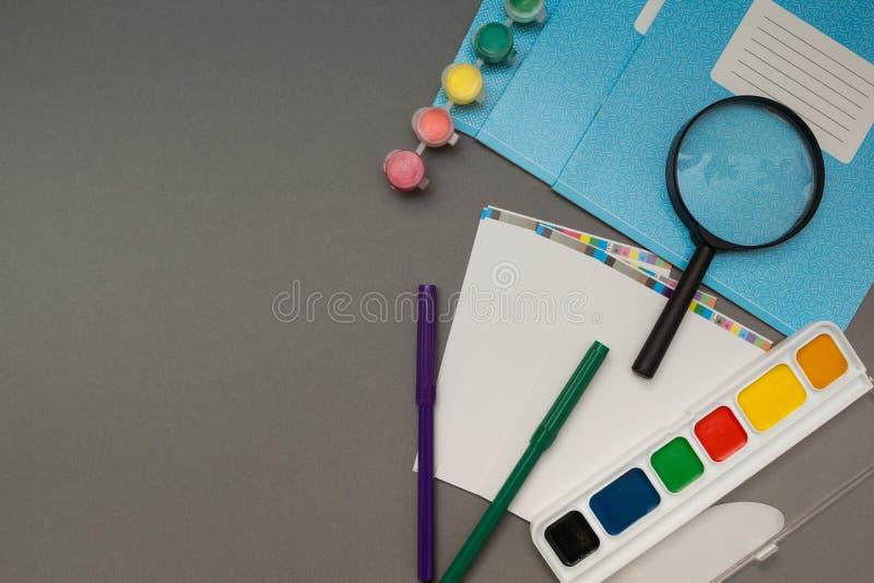 Schulezubehör auf grauem Hintergrund stockbilder