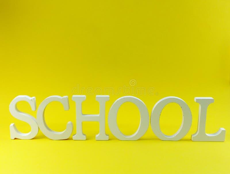 Schulhölzerne Alphabetbuchstaben auf gelbem Hintergrund lizenzfreies stockbild