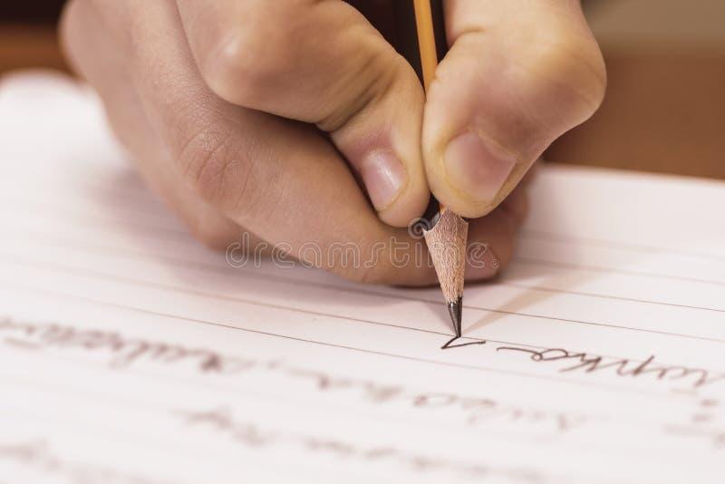 Schuljungen-Schreibens-Abschluss oben Bleistift in der Kinderhand stockfoto