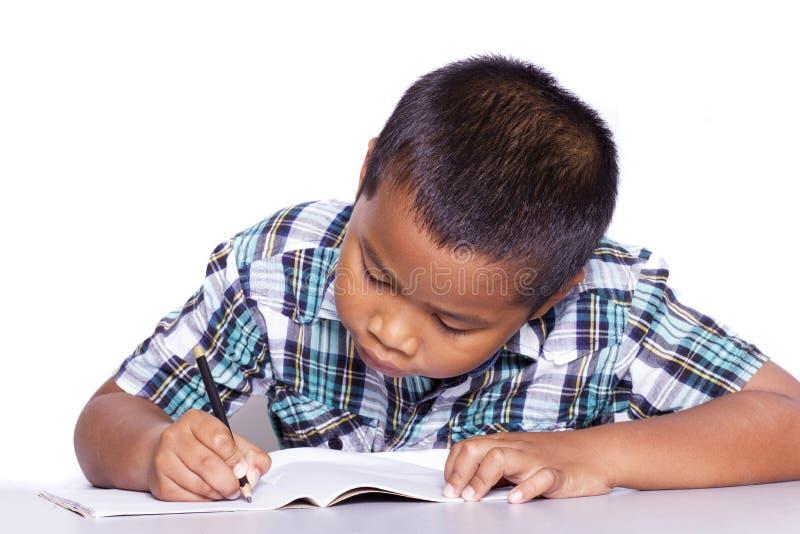 Schuljungensitzen und -schreiben im Notizbuch lizenzfreie stockfotos