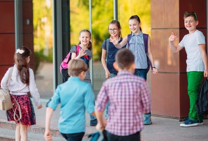 Schulkameraden gehen zu schulen Studenten grüßen sich lizenzfreies stockfoto