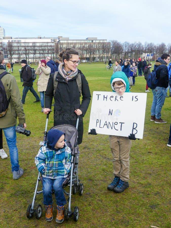 Schulkind am Antiklimawandelprotest in Den Haag mit Fahnen gehend durch die Stadt stockfotografie