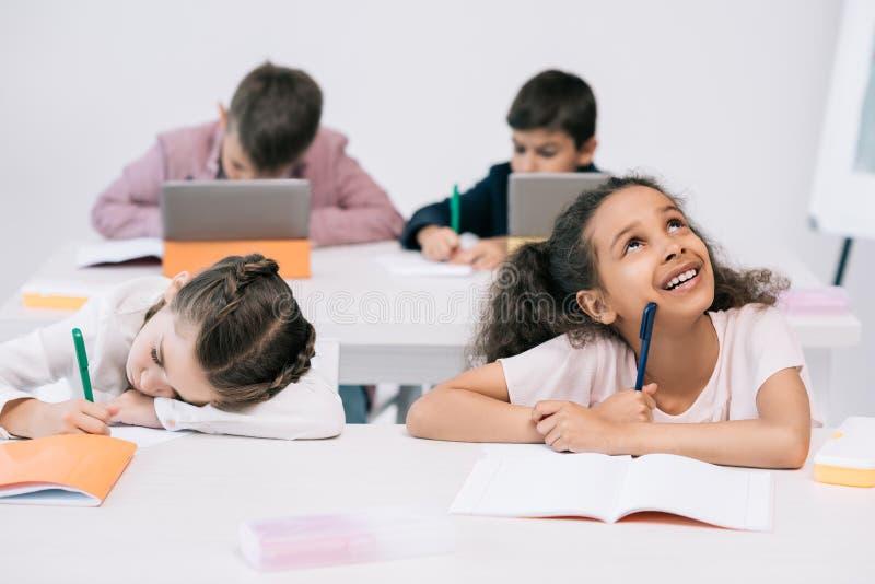 Schulkinder, die in Übungsbücher schreiben und digitale Tabletten im Klassenzimmer verwenden stockfotografie