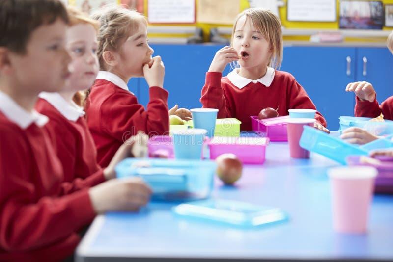 Schulkinder, die bei Tisch sitzen, Lunchpaket essend lizenzfreie stockfotos
