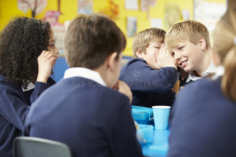 Schulkinder, die bei Tisch sitzen, Lunchpaket essend lizenzfreies stockfoto