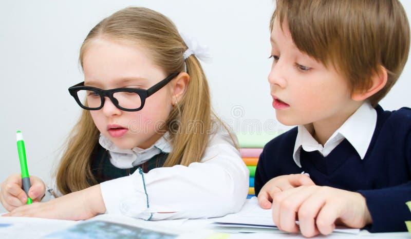 Schulkinder, die an der Schule schreiben lizenzfreie stockfotografie